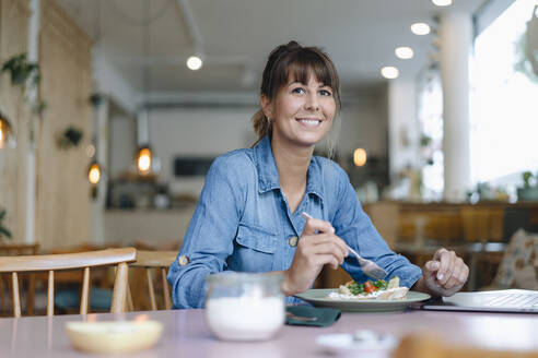 Female owner eating food while sitting in cafe - GUSF04661