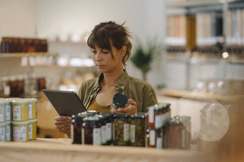 Female owner checking inventory on digital tablet in coffee shop - GUSF04673