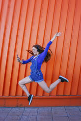 Redhead woman wearing headphones holding mobile phone while jumping in front of orange wall - MGRF00011