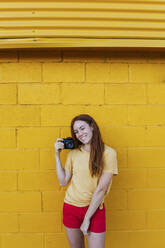 Smiling woman holding camera while standing against yellow wall - MGRF00014