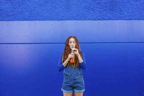 Young woman in blue casual clothing drinking juice while standing against blue wall - MGRF00017