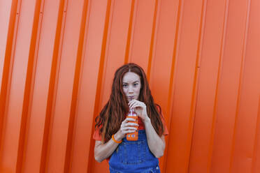 Redhead woman drinking juice while standing against orange wall - MGRF00023