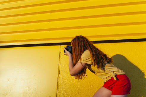 Redhead woman photographing through camera while standing against yellow - MGRF00029