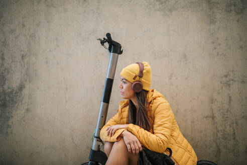 Thoughtful woman listening music through headphones while sitting on electric push scooter against wall - GRCF00439
