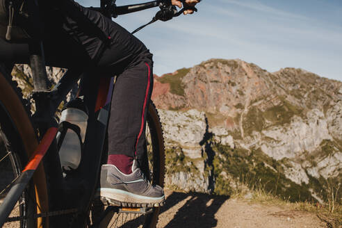 Woman on mountain bike standing against mountain at Somiedo Natural Park, Spain - DMGF00244