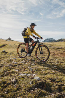 Female mountain biker riding bicycle on mountain at Somiedo Natural Park, Spain - DMGF00253