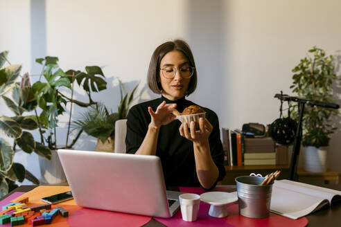 Mid adult businesswoman holding cake while sitting by laptop at home - VABF03812