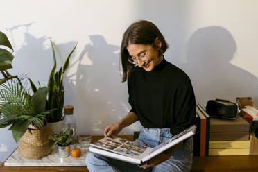 Smiling woman looking photographs in photo album while sitting at home - VABF03815