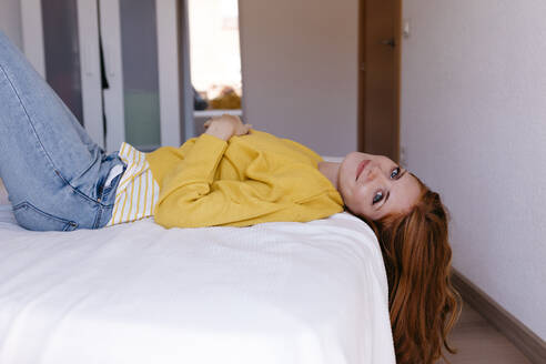 Redhead woman lying down on bed in bedroom at home - TCEF01275