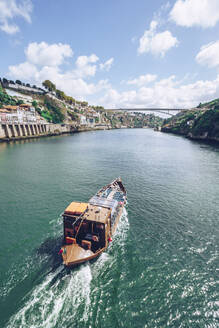 Boat sailing in Douro River against sky, Porto, Portugal - RSGF00391