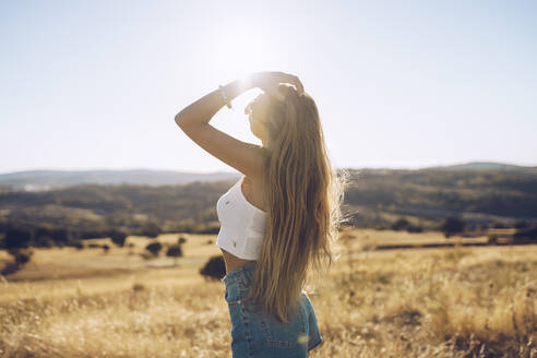 Young woman with hand in hair standing on field against sky during sunny day - RSGF00400