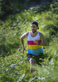 Sportsman looking away while running between grass on mountain at forest - SNF00754