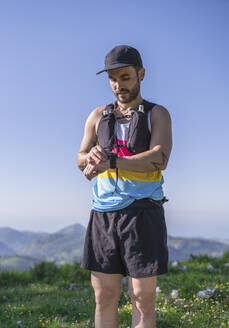 Mid adult man wearing cap and bottle strap checking time on watch while standing on mountain - SNF00760