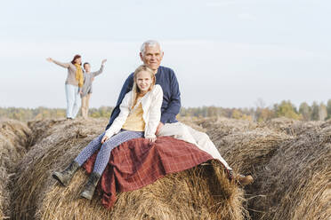 Grandfather and granddaughter sitting on hay bale while grandmother and grandson in background - EYAF01398