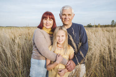 Happy grandparents embracing granddaughter standing at field - EYAF01407