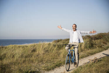 Happy mature man with arms outstretched riding bicycle at beach against clear sky - UUF21973