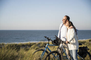 Happy mature couple with bicycles at beach against clear sky during weekend - UUF21988