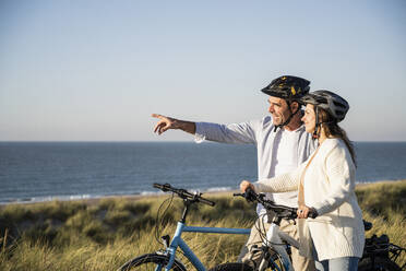 Smiling couple in cycling helmets looking at view while standing on beach against clear sky - UUF21991