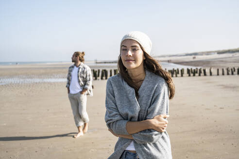 Young woman in standing with eyes closed at beach while man in background - UUF22024