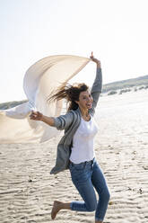 Cheerful woman running while holding blanket at beach on sunny day - UUF22036