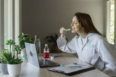 Young female dentist teaching how to brush teeth through video call on laptop at home - AFVF07423