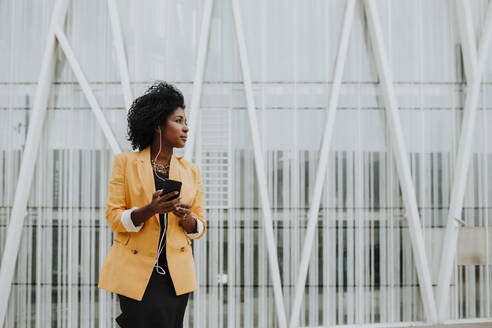 Businesswoman listening music through earphones while looking while standing against building - GMLF00755