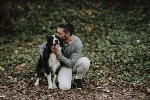 Mature man kissing his dog while sitting at park - GMLF00788