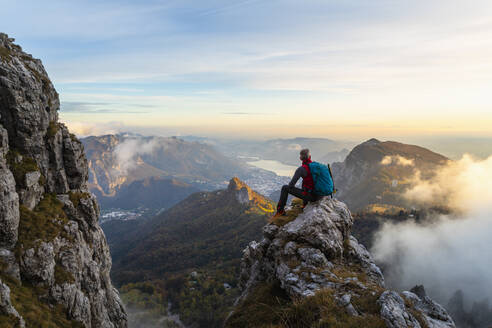 Pensive hiker looking at view while sitting on mountain peak during sunrise at Bergamasque Alps, Italy - MCVF00653