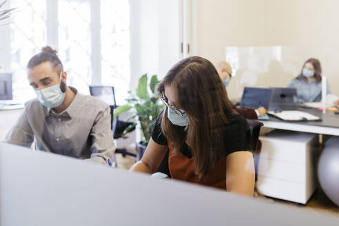 Businesswoman wearing protective face mask while working by coworker at desk in office - JRFF04807