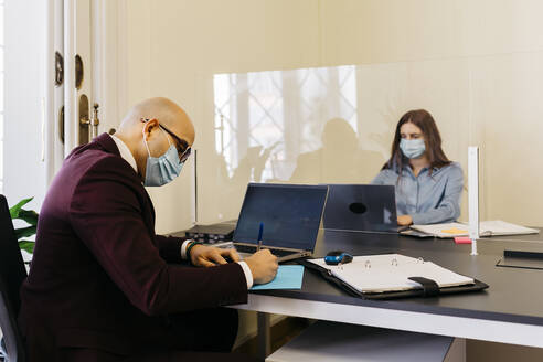 Male and female entrepreneurs with protective mask working in office - JRFF04810