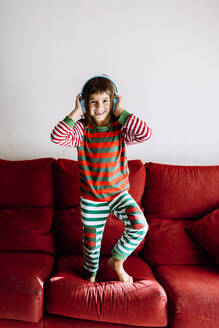 Happy girl listening to music through headphones while standing on sofa at home - XLGF00729