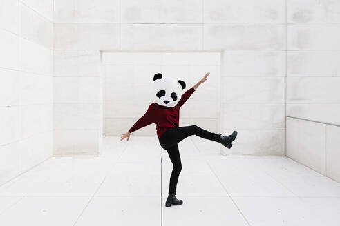 Woman doing with leg up wearing panda mask standing against doorway - XLGF00762