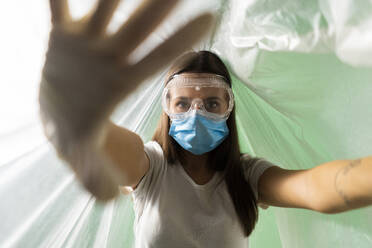 Woman wearing protective face mask doing stop gesture while covered in plastic during coronavirus - GIOF09524