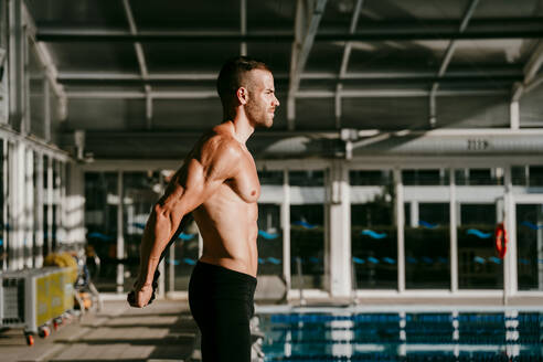 Handsome swimmer doing warm up exercise at poolside - EBBF01281