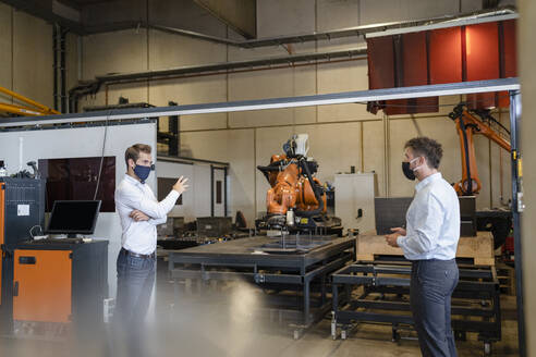 Businessmen with face mask discussing while standing at social distance against robotic arm equipment in factory - DIGF12977