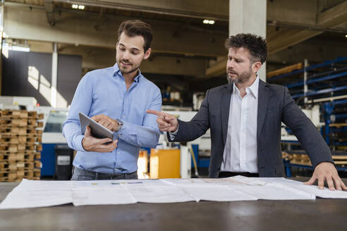 Businessmen using digital tablet while working at factory - DIGF13001