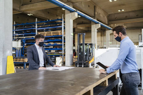 Businessman wearing face mask using digital tablet while standing at social distance with colleague in factory - DIGF13016