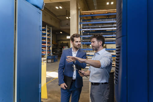 Businessman and colleague with digital tablet having discussion while standing at factory - DIGF13052