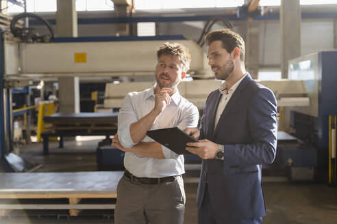 Businessmen with digital tablet looking away while standing at factory - DIGF13061