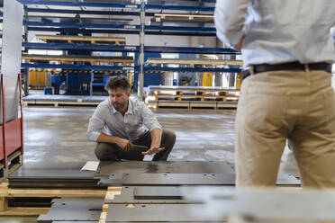 Businessman checking metal while working with colleague at factory - DIGF13079
