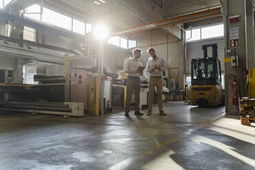 Business people working while standing at factory - DIGF13082
