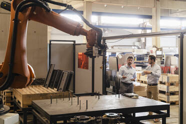 Business people discussing while looking at automated robotic arm at factory - DIGF13091