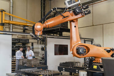 Automatic robotic arm machine with businessmen standing in background at factory - DIGF13094