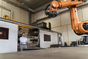 Businessman with arms crossed monitoring automatic robot arm while standing at factory  - DIGF13097