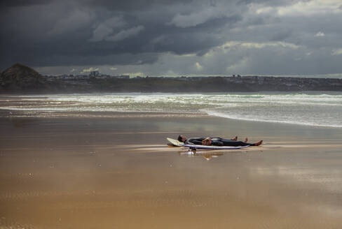 Male friends resting on surfboards at beach during cloudy day - AJOF00520