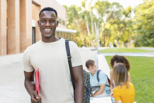 Smiling confident male student with folder standing in university campus - IFRF00021