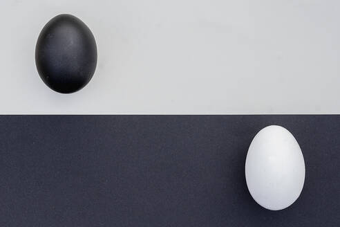 Studio shot of black and white eggs on contrasting backgrounds - ZMF00502