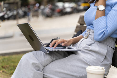 Woman surfing internet on laptop while sitting over bench - AFVF07519