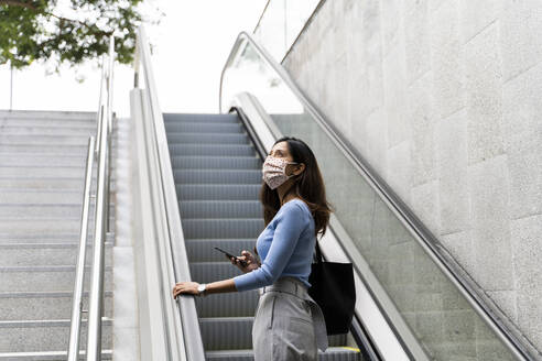 Contemplating woman looking up with mobile phone while standing on escalator during COVID-19 - AFVF07525