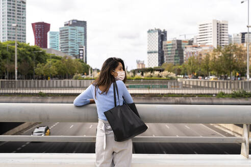 Rear view of woman with purse standing against railing in city during COVID-19 - AFVF07540